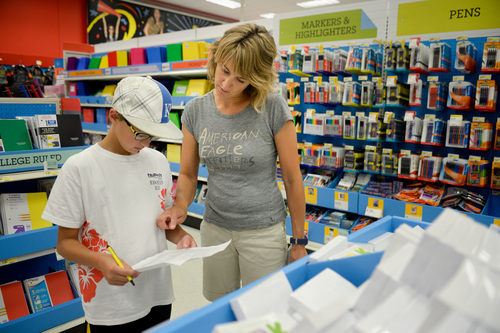FILE - In this July 30, 2014 file photo, Jill Courtney, right, shops for school supplies for her sons, Will, left, and Reid, not seen, at a Target store in St. Joseph, Mo. The National Retail Federation, the nation's largest retail industry trade organization, expects the average family with children from kindergarten through grade 12 will spend $669.28 on clothing, shoes, supplies and electronics for the back-to-school season, up 5 percent from $634.78 last year. (AP Photo/St. Joseph News-Press, Sait Serkan Gurbuz, File)