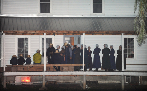 Supporters gather on the porch of a house at the intersection of Route 812 and Mt. Alone Road in Heuvelton, NY on Thursday, Aug. 14, 2014 after Fannie Miller, 12, and her sister Delila Miller, 6, were returned home safely after being abducted Wednesday night at a farm stand near their home. (AP Photo/The Watertown Daily Times, Jason Hunter)