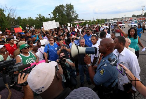 CHANGES THE WORD SEIZED TO TOOK - Missouri State Highway Patrol Capt. Ronald Johnson addresses the crowd of protesters, asking them to stay on the sidewalk and not block traffic Thursday, Aug. 14, 2014, in Ferguson, Mo. The Missouri Highway Patrol seized took of a St. Louis suburb Thursday, stripping local police of their law-enforcement authority after four days of clashes between officers in riot gear and furious crowds protesting the death of an unarmed black teen shot by an officer. (AP Photo/St. Louis Post-Dispatch, David Carson)