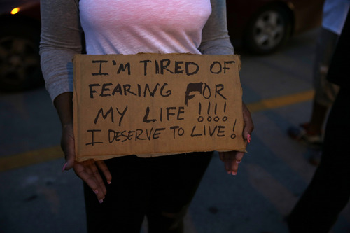 A demonstrator holds a sign Thursday, Aug. 14, 2014, in Ferguson, Mo.  Hundreds of people protesting the death of  Michael Brown marched through the streets of Ferguson alongside state troopers Thursday. (AP Photo/Jeff Roberson)
