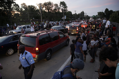 Demonstrators line the streets as traffic slowly moves past Thursday, Aug. 14, 2014, in Ferguson, Mo. Hundreds of people protesting the death of the black Missouri teenager shot by a white police officer marched through the streets of Ferguson alongside state troopers Thursday. (AP Photo/Jeff Roberson)