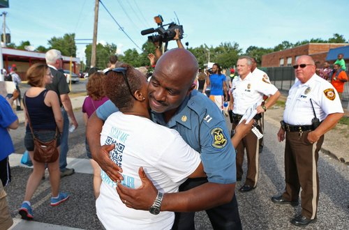 Capt. Ronald Johnson of the Missouri Highway Patrol hugs Angela Whitman, of Berkeley, Mo., on West Florissant Avenue in Ferguson, Mo., on Thursday, Aug. 14, 2014. The Missouri Highway Patrol took control of the St. Louis suburb Thursday, stripping local police of their law-enforcement authority after four days of clashes between officers in riot gear and furious crowds protesting the death of an unarmed black teen shot by an officer. (AP Photo/St. Louis Post-Dispatch, David Carson)
