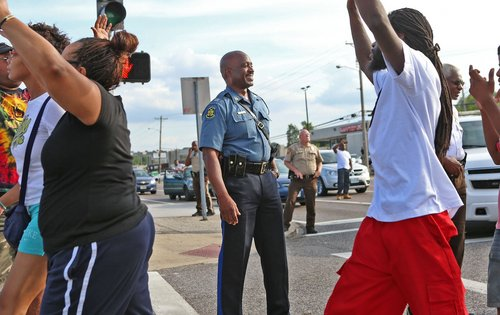 Capt. Ronald Johnson of the Missouri Highway Patrol smiles at demonstrators march along West Florissant Avenue in Ferguson, Mo., on Thursday, Aug. 14, 2014. The Missouri Highway Patrol seized control of a St. Louis suburb Thursday, stripping local police of their law-enforcement authority after four days of clashes between officers in riot gear and furious crowds protesting the death of an unarmed black teen shot by an officer. (AP Photo/St. Louis Post-Dispatch, David Carson)