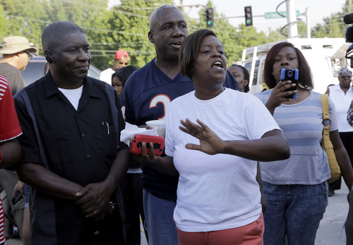 People react after Ferguson Police Chief Thomas Jackson releases the name of the the officer accused of fatally shooting Michael Brown, an unarmed black teenager, Friday, Aug. 15, 2014, in Ferguson, Mo. The officer's name is Darren Wilson, a six-year veteran of the force. (AP Photo/Jeff Roberson)