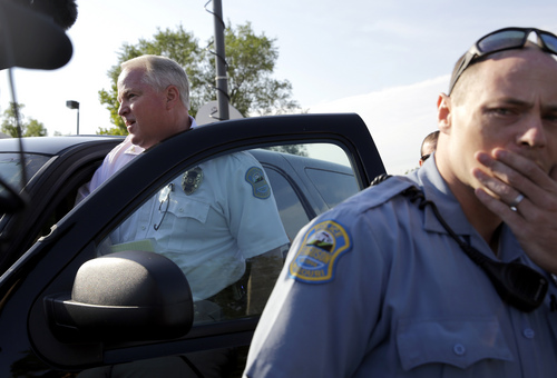 Ferguson Police Chief Thomas Jackson, left, gets in a vehicle to drive away after releasing the name of the the officer accused of fatally shooting Michael Brown, an unarmed black teenager, during a news conference Friday, Aug. 15, 2014, in Ferguson, Mo.  Jackson announced that the officer's name is Darren Wilson. (AP Photo/Jeff Roberson)