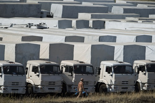 A driver carries empty water bottles as he walks past trucks forming part of an aid convoy parked in a field about 28 kilometers (17 miles) from the Ukrainian border, near Kamensk-Shakhtinsky, Rostov-on-Don region, Russia, Saturday, Aug. 16, 2014. Hundreds of trucks in a Russian aid convoy are waiting near the Ukrainian border as complicated procedures drag on for allowing them into eastern Ukraine to help civilians suffering amid fighting between Ukrainian forces and separatists. (AP Photo/Pavel Golovkin)