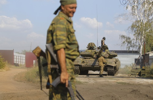 Pro-Russian rebels park a tank on their base near the town of Krasnodon, eastern Ukraine, Saturday, Aug. 16, 2014. Tanks and APC's manoeuvre on the Ukrainian side of Ukrainian-Russia border as the humanitarian convoy on the other side of the frontier is still unmoved. (AP Photo/Sergei Grits)