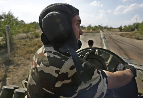 A Pro-Russian rebel rides on a tank near the town of Krasnodon, eastern Ukraine, Saturday, Aug. 16, 2014.  Tanks and APC's manoeuvre on the Ukrainian side of Ukrainian-Russia border as the humanitarian convoy on the other side of the frontier is still unmoved. (AP Photo/Sergei Grits)