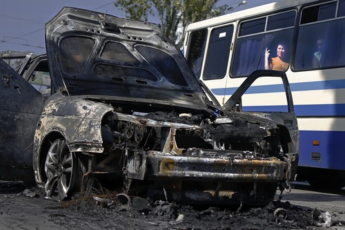 Passengers look through a bus window at destroyed car after shelling in Donetsk, eastern Ukraine, Saturday, Aug. 16, 2014.The fighting in eastern Ukraine has claimed nearly 2,100 lives, according to the United Nations, with half of those in the last few weeks as the Ukrainian troops regained more and more rebel-held territory. (AP Photo/Max Vetrov)