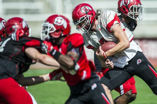 Chris Detrick  |  The Salt Lake Tribune Utah Utes quarterback Travis Wilson (7) runs the ball past Utah Utes linebacker Pita Taumoepenu (50) during a scrimmage at Rice-Eccles Stadium DOW} April 12, 2014.