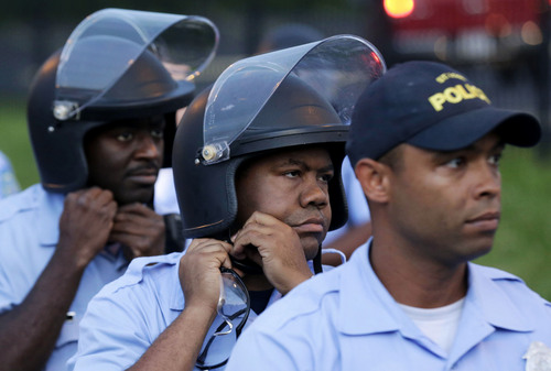 Police in riot gear prepare to take up positions Saturday, Aug, 16, 2014, as people protest the police shooting death of Michael Brown a week ago in Ferguson, Mo. Despite heavy rainfall and lightning, hundreds of protesters gathered Saturday night at a busy thoroughfare that has been the site of previous clashes with police. Dozens of officers, a much more visible presence than the night before, stood watch — including some with shields. (AP Photo/Charlie Riedel)