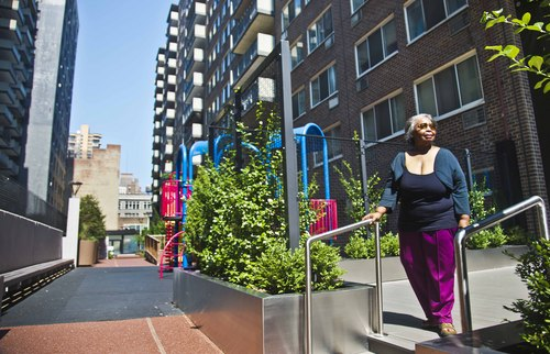 In this Aug. 5, 2014 photo, Jean Green Dorsey walks outside the building on New York City's Upper West Side where she has lived since 1972. Dorsey has a rent stabilized unit in a building that also houses market rate residents. As a rent stabilized tenant, Dorsey is not allowed to use the new gym that market rate residents use for free, even if she paid for the privilege. (AP Photo/Bebeto Matthews)