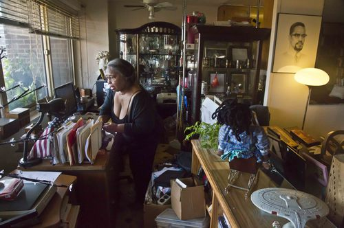 In this Aug. 5, 2014 photo, Jean Green Dorsey, a rent-stabilized tenant in a building on New York City's Upper West Side, looks for documents on her desk.  Dorsey and her late husband, astronomer, Dr. William Dorsey, moved to the apartment in 1972. Although she has been in the building in excess of 40 years, Dorsey is unable to avail herself of some of its amenities that market residents enjoy. (AP Photo/Bebeto Matthews)