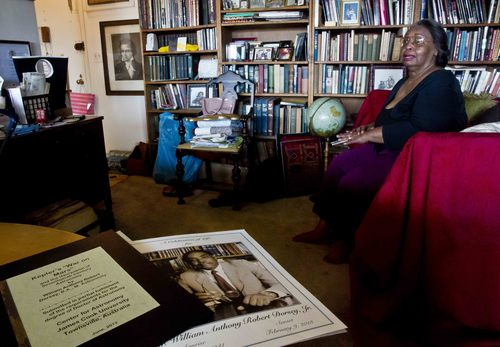 In this Aug. 5, 2014 photo Jean Green Dorsey, is seated among shelves of books at her rent-stabilized apartment in New York City's Upper West Side. Dorsey, who has lived in the apartment since 1972, is among a growing group of New Yorkers who reside in the same building with market rate residents, but aren't allowed to use amenities such as improved entranceways or fitness facilities that market rate residents enjoy. (AP Photo/Bebeto Matthews)