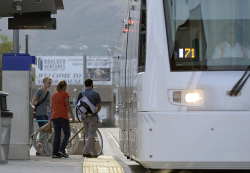 Al Hartmann  |  The Salt Lake Tribune  Folks climb aboard the Sugar House streetcar at the 900 East stop Wednesday August 13, 2014.  It is only slightly faster than the nearby parallel bus, and pedestrians sometimes can outrace it. Far fewer people than projected are riding it. And it was expensive, $37 million. But officials still see it as a success and worth the price because of the economic development it has attracted.
