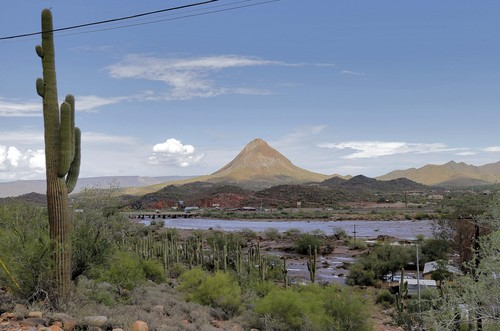 Flash flood waters that overran Skunk Creek continue to run, Tuesday, Aug. 19, 2014, through New River, Ariz., just northwest of Phoenix. (AP Photo/Matt York)