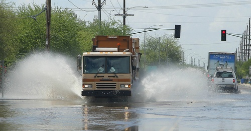 Vehicles drive through flooded streets as strong storms moved through the Phoenix metro area on Tuesday, Aug. 19, 2014. (AP Photo/Ross D. Franklin)