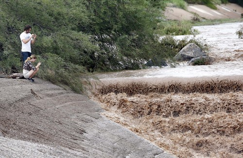 Thomas Ingersoll and Sydney Cisco watch flash flood waters from the Sonoran Desert overrun Skunk Creek, Tuesday, Aug. 19, 2014, in northwestern Phoenix. (AP Photo/Matt York)