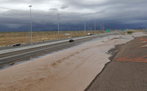Flash flood waters from the overrun Skunk Creek flood I-10, Tuesday, Aug. 19, 2014, in northwestern Phoenix. Flooding from heavy rain in the Phoenix area has forced authorities to close several major roads, including a portion of Interstate 17 about 25 miles north of the city. (AP Photo/Matt York)