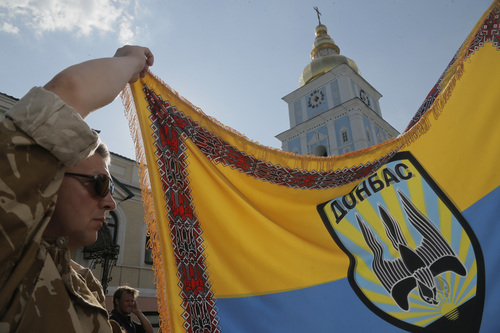 An officer of volunteer battalion 'Donbas' holds battalion colours during a blessing ceremony in St. Michael Cathedral in Kiev, Ukraine, Tuesday, Aug. 19, 2014.  Ukrainian government troops were fighting pro-Russian rebels in the streets of Luhansk on Tuesday and captured most of a town near the eastern city of Donetsk, tightening the noose around that key rebel-held stronghold, Ukrainian officials said. Commander of the Donbass battalion, Semyon Semenchenko was wounded during fighting Tuesday. He said government soldiers had destroyed three rebel checkpoints and four firing positions and that fighting continued. (AP Photo/Efrem Lukatsky)