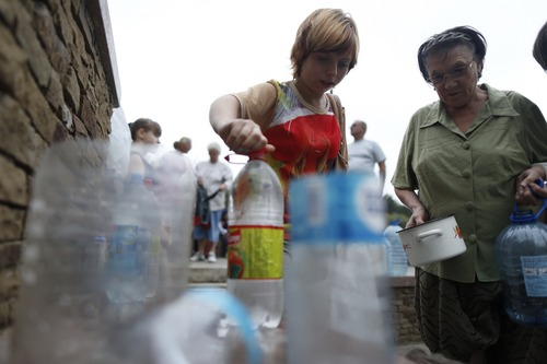 Local citizens line up to collect water on a street in Donetsk, Ukraine, Monday, Aug. 18, 2014. The Ukrainian government and the pro-Russian rebels have traded accusations on numerous occasions before, and it was not possible to immediately reconcile the differing statements, since the war zone is very dangerous for journalists and a lack of power there limits independent reports from civilians. (AP Photo/Max Vetrov)
