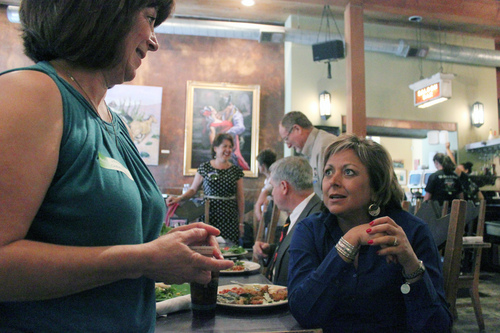 New Mexico Gov. Susana Martinez, right, takes a break from lunch to talk about green chile during a visit to The Range restaurant in Bernalillo, N.M., on Tuesday, Aug. 19, 2014. The restaurant is the first to sign up to participate in a new certification program unveiled Tuesday to protect the integrity and reputation of New Mexico-grown chile, a signature crop that infuses about $400 million into the state's economy each year. (AP Photo/Susan Montoya Bryan)
