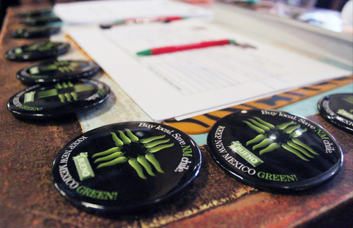 Officials give out buttons before unveiling a new certification program aimed at protecting the reputation and integrity of New Mexico-grown chile during an event at The Range restaurant in Bernalillo, N.M., on Tuesday, Aug. 19, 2014. The Range is the first restaurant to sign up to participate in the program. (AP Photo/Susan Montoya Bryan)