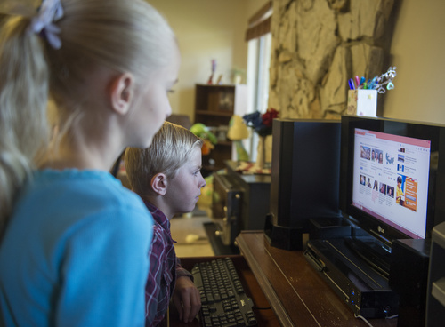 Rick Egan  |  The Salt Lake Tribune  Ivy Hammon 10,  and Peter Hammon, 12, check out  the internet from their Riverton home, Monday, August 18, 2014.  The Hammon family could not afford the internet without the special deal from Comcast.