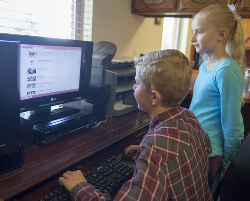 Rick Egan  |  The Salt Lake Tribune  Peter Hammon, 12, and Ivy Hammon 10, check out  the internet from their Riverton home, Monday, August 18, 2014.  The Hammon family could not afford the internet without the special deal from Comcast.