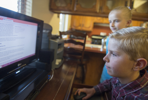 Rick Egan  |  The Salt Lake Tribune Peter Hammon, 12, and Ivy Hammon 10, check out  the Internet from their Riverton home on Monday. The Hammon family could not afford the Internet without the special deal from Comcast.