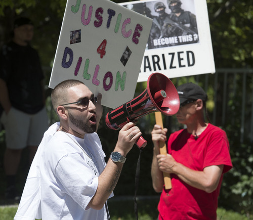 Steve Griffin  |  The Salt Lake Tribune   Aaron Swanenberg speaks through a blow horn during a protest about the police shooting of Dillon Taylor in Salt Lake City, Monday, August 18, 2014. Swananberg was a family friend of Taylor's.