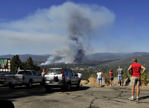 A fire creates a plume of smoke watched by onlookers along Highway 41 south of Oakhurst, Calif., Monday, Aug. 18, 2014. One of several wildfires burning across California prompted the evacuation of hundreds of people in a central California foothill community near Yosemite National Park, authorities said. (AP Photo/The Fresno Bee, Eric Paul Zamora)