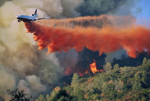 An air tanker drops fire retardent on a fire which was burning on a ridge northeast of Oakhurst, Calif., Monday, Aug. 18, 2014. One of several wildfires burning across California prompted the evacuation of hundreds of people in a central California foothill community near Yosemite National Park, authorities said. (AP Photo/The Fresno Bee, Eric Paul Zamora)