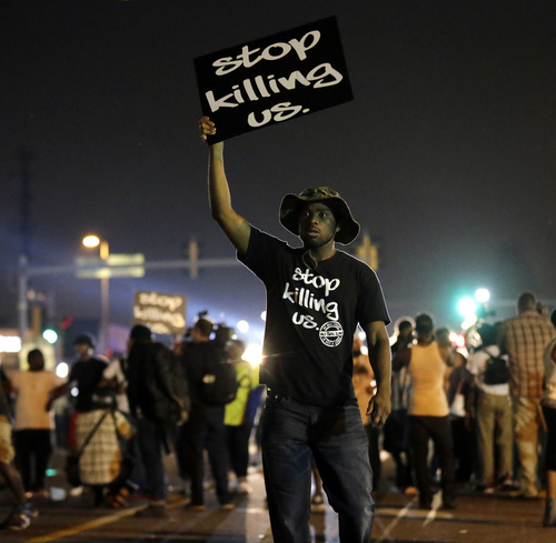 People walk through the streets after a standoff with police Monday, Aug. 18, 2014, during a protest for Michael Brown, who was killed by a police officer Aug. 9 in Ferguson, Mo. Brown's shooting has sparked more than a week of protests, riots and looting in the St. Louis suburb. (AP Photo/Charlie Riedel)