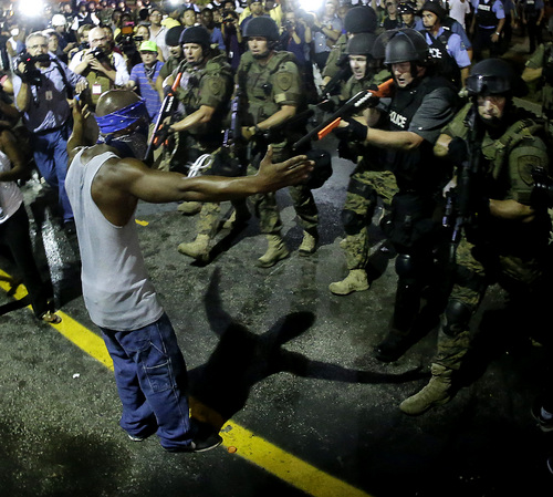 Police arrest a man as they disperse a protest in Ferguson, Mo. early Wednesday, Aug. 20, 2014. On Saturday, Aug. 9, 2014, a white police officer fatally shot Michael Brown, an unarmed black teenager, in the St. Louis suburb. (AP Photo/Charlie Riedel)