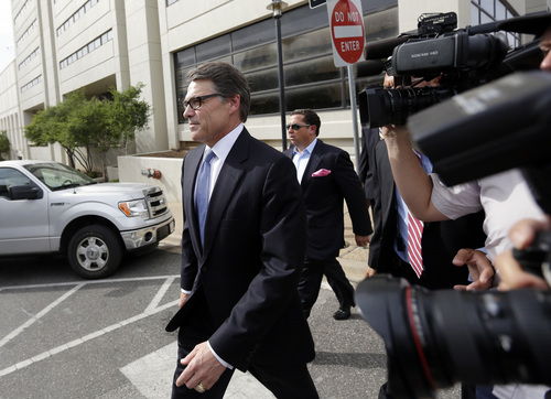 Texas Gov. Rick Perry, left, leaves the Blackwell Thurman Criminal Justice Center after he was booked, Tuesday, Aug. 19, 2014, in Austin, Texas. Perry was indicted last week on charges of coercion and official oppression for publicly promising to veto $7.5 million for the state public integrity unit run. (AP Photo/Eric Gay)