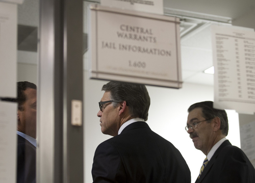 Texas Gov. Rick Perry, middle, is booked at the Blackwell-Thurman Criminal Justice Center in Austin, Texas, for two felony indictments of abuse of power on Tuesday, Aug. 19, 2014, in Austin, Texas. (AP Photo/Austin American-Statesman, Jay Janner)