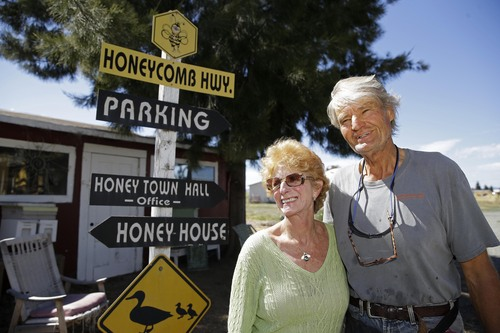 In this Tuesday, July 22, 2014 photo, Helene and Spenser Marshall stand outside their Marshall's Farm Honey in American Canyon, Calif. California's record three-year drought has left hillsides barren and forced farmers to tear out orchards and leave fields fallow. Beekeepers are scrambling to find new flowers for their hives, feeding them artificial nectar or sending them out of state. (AP Photo/Eric Risberg)