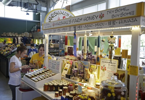 In this Tuesday, July 22, 2014 photo, a woman buys an assortment of flavored honey straws at the Marshall's Farm Honey stand at the Oxbow Public Market in Napa, Calif. California's record three-year drought has left hillsides barren and forced farmers to tear out orchards and leave fields fallow. Beekeepers are scrambling to find new flowers for their hives, feeding them artificial nectar or sending them out of state. (AP Photo/Eric Risberg)