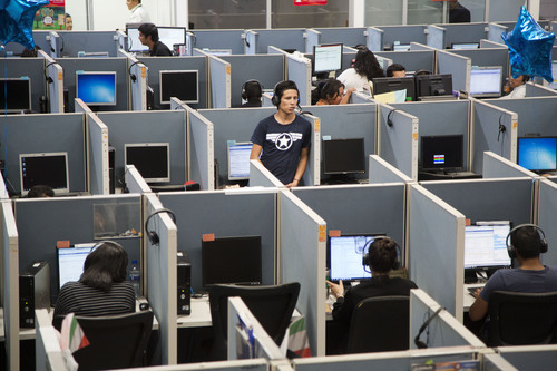 In this Aug. 13, 2014 photo, a man stands in the middle of the Firstkontact Center, a call center in the northern border city of Tijuana, Mexico. Many Mexicans deported under U.S. President Barack Obama are finding employment in call centers in Tijuana and other border cities. In perfect English, some don't even speak Spanish, they talk to American consumers who buy gadgets and gizmos, have questions about warrantees and complain about overdue deliveries. The call center industry has prospered in Mexican border cities as deportations spiked under U.S. President Barack Obama. (AP Photo/Alex Cossio)