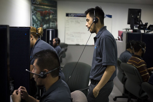 In this Aug. 13, 2014 photo, men work the phones at  the Firstkontact Center, a call center in the northern border city of Tijuana, Mexico. Many Mexicans deported under U.S. President Barack Obama are finding employment in call centers in Tijuana and other border cities. Firstkontact Center, where about 200 of nearly 500 employees were deported, opened a second building this year in an industrial area to more than double its capacity. More than 100 people in a warehouse-like room sell transmissions and brakes for U.S. Auto Parts Network Inc. (AP Photo/Alex Cossio)