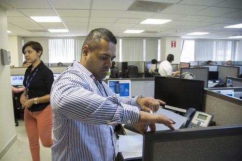 In this Aug. 18, 2014 photo, Henry Monterroso, 34, works at the Call Center Services International, a call center in the northern border city of Tijuana, Mexico. Monterroso is a foreigner in his own country, he was raised in California after he entered the U.S. illegally with his mother when he was 5 years old and was later deported to Mexico in 2011. (AP Photo/Alex Cossio)