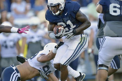 Chris Detrick  |  The Salt Lake Tribune Brigham Young Cougars running back Jamaal Williams (21) runs the ball past Brigham Young Cougars linebacker Toloa'i Ho Ching (98) during a scrimmage at LaVell Edwards Stadium Friday August 15, 2014.