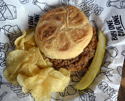 "Al Hartmann  |  The Salt Lake Tribune  Even Stevens' Sloppy Joe with beef and chrorizo, slow simmered in ""slopp"" sauce, pickled red onion on a Kaiser roll with chips and dill pickle."