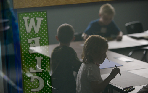 Francisco Kjolseth  |  The Salt Lake Tribune Lights are kept off to keep students calm as they work through a lesson in Rebekah Thomas' first-grade class at Spectrum Academy in Pleasant Grove. The charter school, which primarily caters to students with autism, started their first day of classes on Tuesday, Aug. 19, at Spectrum's second campus.