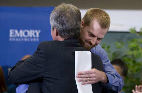 Ebola victim Dr. Kent Brantly, right, hugs a member of the medical staff that treated him, after being released from Emory University Hospital Thursday, Aug. 21, 2014, in Atlanta. Another American aid worker, Nancy Writebol, who was also infected with the Ebola virus, was released from the hospital Tuesday. (AP Photo/John Bazemore)