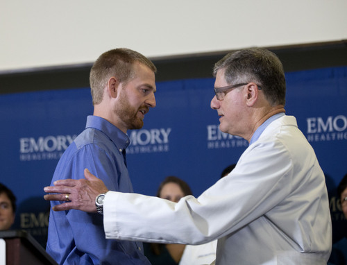 Ebola victim Dr. Kent Brantley, left,  embraces Dr. Bruce Ribner medical director of Emory's Infectious Disease Unit, after being released from Emory University Hospital, Thursday, Aug. 21, 2014, in Atlanta. (AP Photo/John Bazemore)