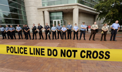 Police guard the entrance to the Buzz Westfall Justice Center in Clayton, Mo., Wednesday, Aug. 20, 2014, where a grand jury is expected to convene to consider possible charges against the Ferguson, Mo. police officer who fatally shot 18-year-old Michael Brown. Brown's shooting in the middle of a street has sparked a more than week of protests, riots and looting in the St. Louis suburb. (AP Photo/Charlie Riedel)