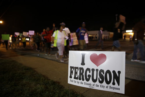 Protesters march Thursday, Aug. 21, 2014, in Ferguson, Mo. Protesters again gathered Thursday evening, walking in laps near the spot where Michael Brown was shot. Some were in organized groups, such as clergy members. More signs reflected calls by protesters to remove the white prosecutor from the case.  (AP Photo/Jeff Roberson)
