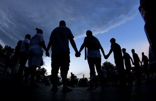 People stand in prayer after marching about a mile to the police station to protest the shooting of Michael Brown Wednesday, Aug. 20, 2014, in Ferguson, Mo. Brown's shooting in the middle of a street Aug 9, by a Ferguson policeman has sparked a more than week of protests, riots and looting in the St. Louis suburb. (AP Photo/Charlie Riedel)